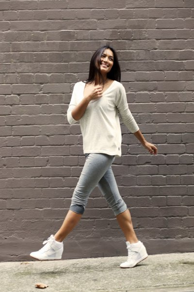 white sweater with scoop neckline and gray knee-length skinny jeans