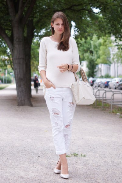 white sweater with scoop neckline and matching boyfriend jeans with ripped edges