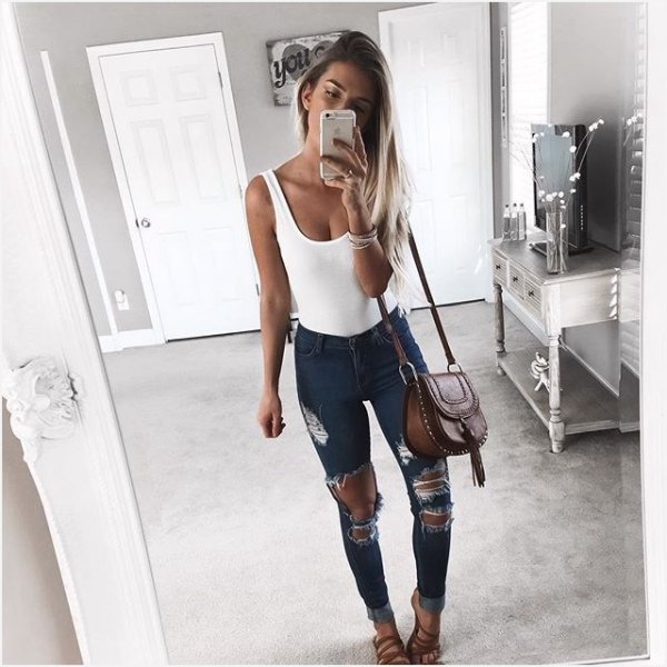 white tank top with scoop neckline and heavily ripped dark gray skinny jeans