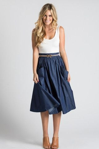 white tank top with scoop neckline and dark blue pleated midi skirt with belt and front pockets