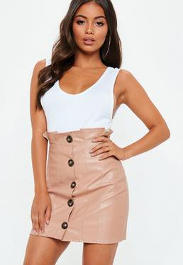 white tank top with scoop neckline and pink mini skirt with high waist and button placket