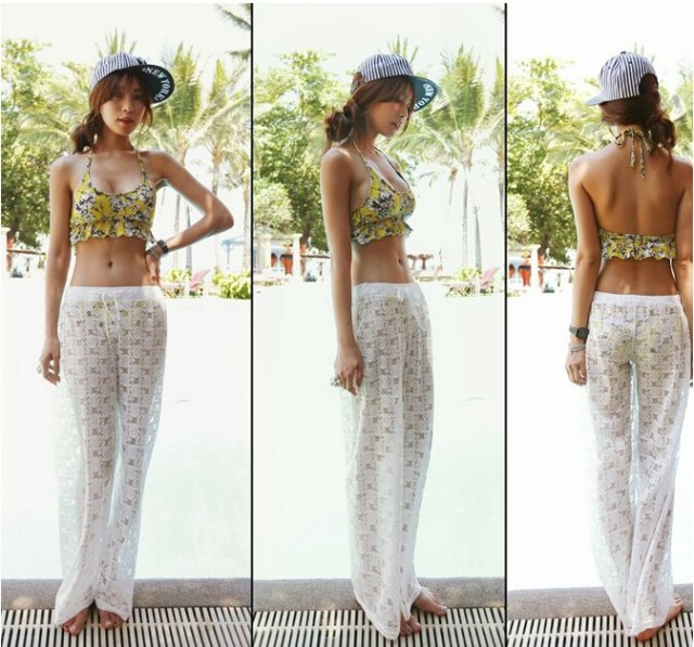 white, semi-transparent beach pants with wide legs and lace over a yellow bikini