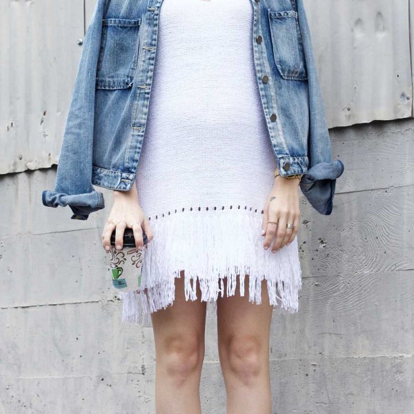 white denim jacket with a shift dress over the shoulders