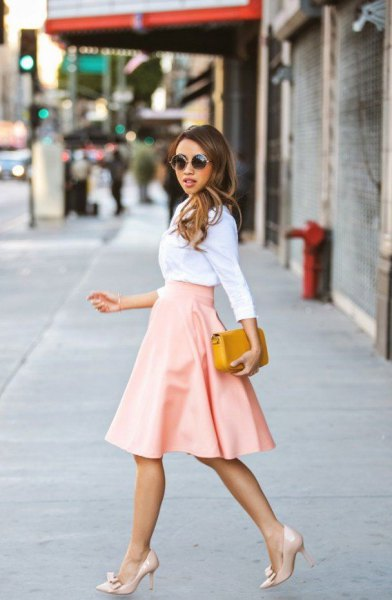 White shirt with a high-waisted, flared, pink skirt made of midi leather