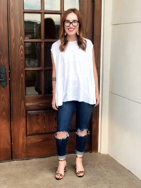 white sleeveless blouse with ripped dark jeans
