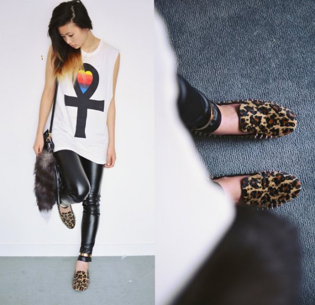 white sleeveless graphic t-shirt with black leather gaiters and leopard print slippers