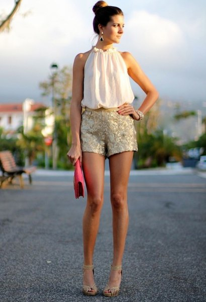 white sleeveless chiffon blouse with mock neck and silver mini shorts with sequins