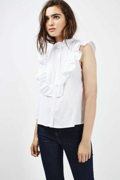 white sleeveless ruffled shirt with black skinny jeans