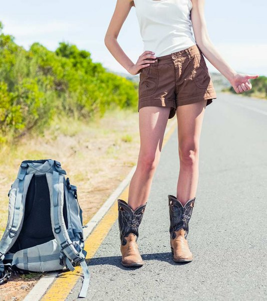 white sleeveless t-shirt with green khaki shorts and square toe boots with a wide calf print