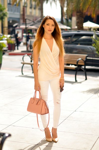 white sleeveless, draped blouse with V-neckline and matching skinny jeans