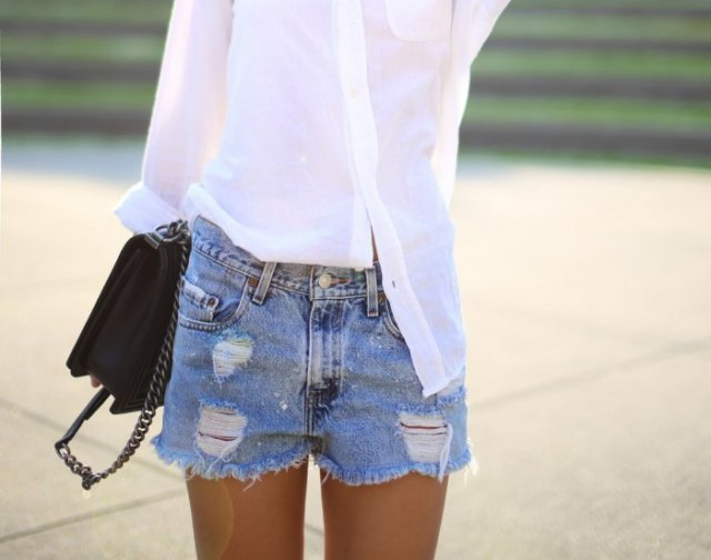 white, narrow-cut shirt with light blue, high-waisted denim shorts in distressed look
