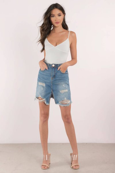Ribbed tank top with white spaghetti strap and deep V-neckline and blue knee-length shorts