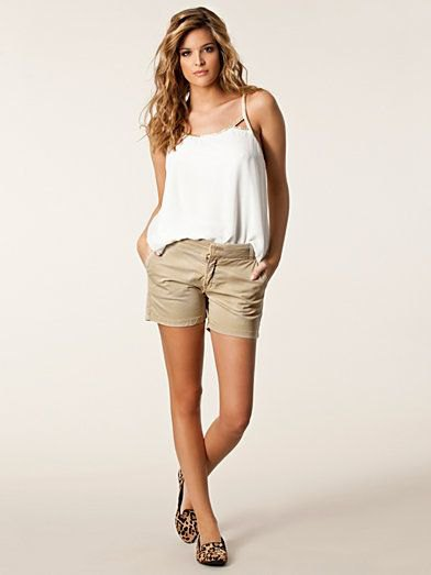 white top with spaghetti straps and beige chino shorts