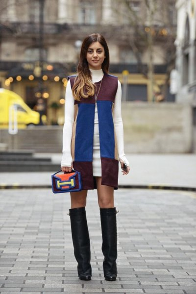 white sweater dress with sleeveless leather jacket in black and blue