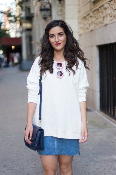 white sweater with blue denim mini skirt and leather handbag