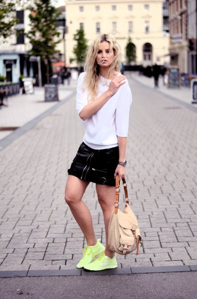 white sweatshirt with black mini skirt and yellow sneakers