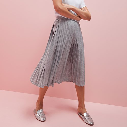 white t-shirt with a light gray pleated skirt and silver evening shoes