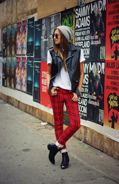 white t-shirt with black leather vest and red checked pants