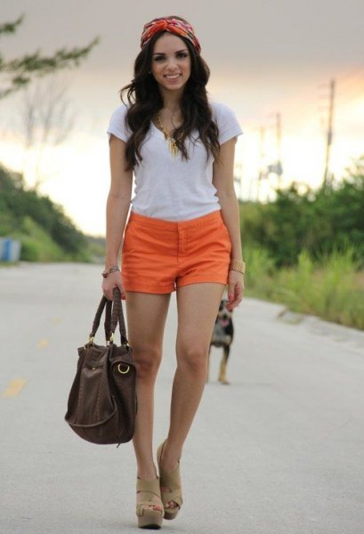 white t-shirt with orange shorts and bare sandals