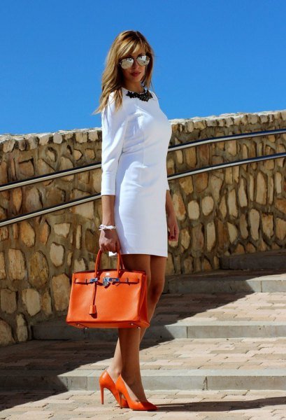 white mini shift dress with three-quarter sleeves and orange leather handbag