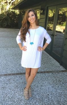 white tunic dress with three-quarter sleeves and bare strappy sandals