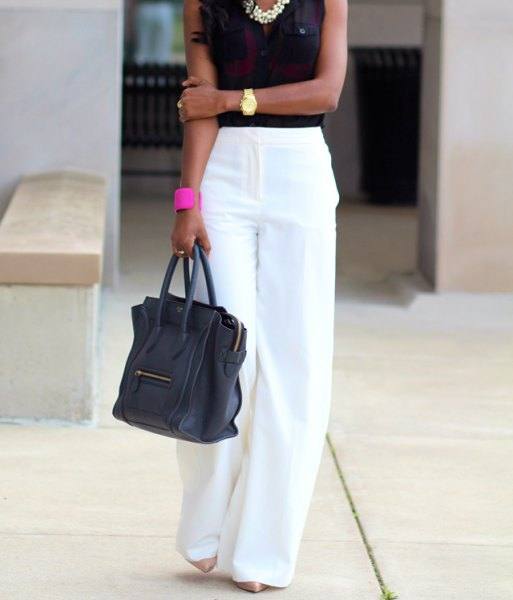 white pants with black sleeveless blouse and statement chain