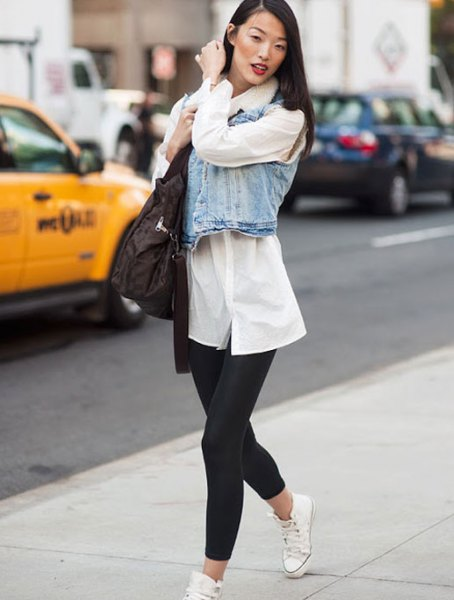 white tunic shirt with buttons, denim vest and black short leggings