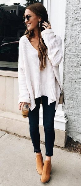 white, chunky autumn sweater with V-neck and black-cut skinny jeans