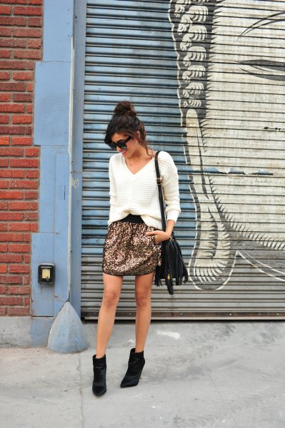 white comfortable sweater with V-neckline, sequin mini skirt and black short boots