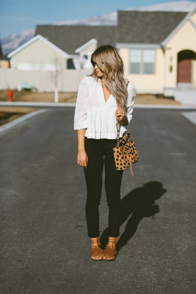 white peplum blouse with V-neckline and black sleeves and black skinny jeans