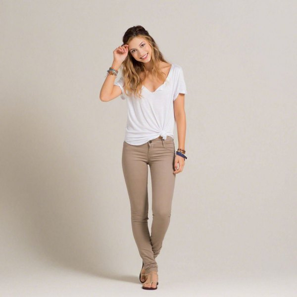 white knotted V-neck t-shirt and gray-green super skinny jeans