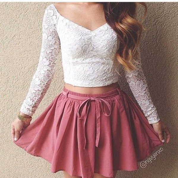 long-sleeved white lace crop top with a v-neckline and pink skater skirt