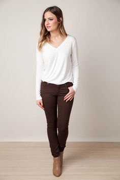 white long-sleeved V-neck t-shirt, brown jeans and ankle boots