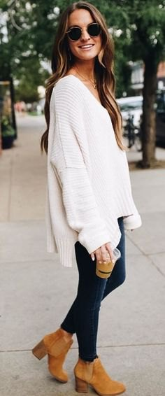 white oversized V-neck sweater and suede ankle boots with camel heel