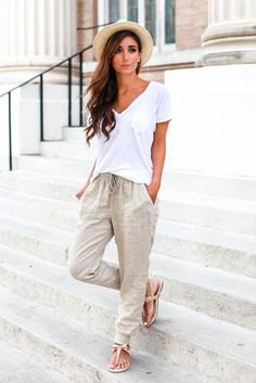 white V-neck shirt and light pink linen pants with an elastic waist
