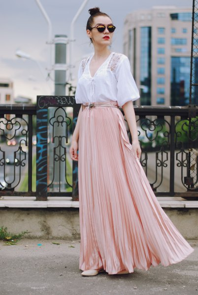white short-sleeved blouse with V-neckline and light pink, flowing skirt