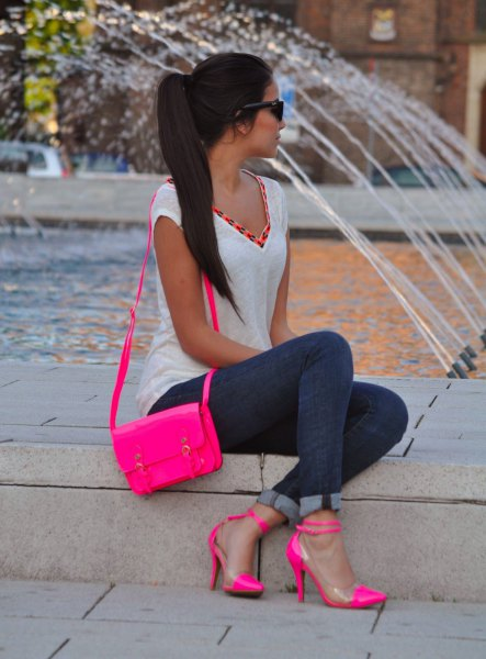 Slim fit top with white V-neckline, skinny jeans with cuffs and pink heels