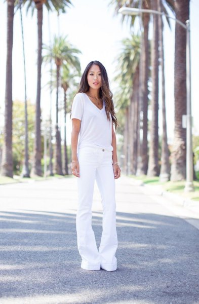 white V-neck t-shirt and white jeans with a bell bottom