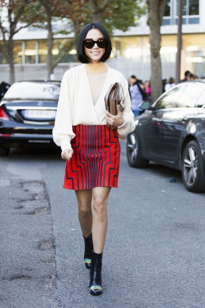 white wrap sweater with V-neck, red graphic skirt and mini boots