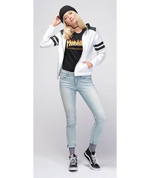 white windbreaker with black graphic t-shirt and light blue skinny jeans