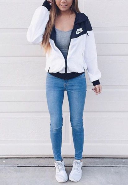 white windbreaker with gray, figure-hugging tank top and blue skinny jeans
