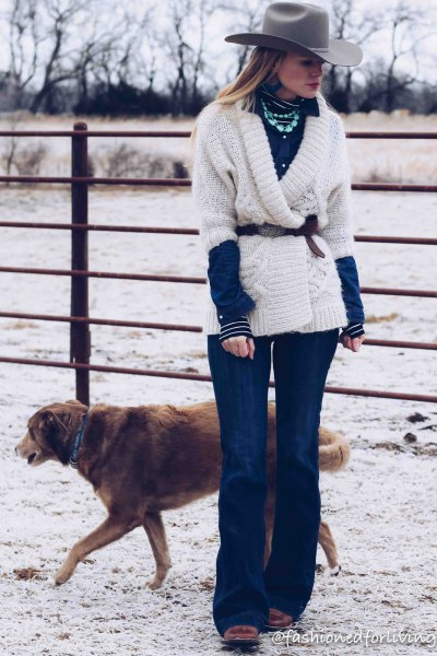 white wrap sweater with belt, blue flared jeans and black square toe boots