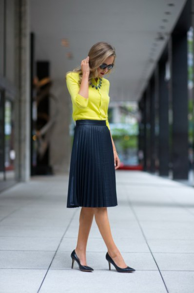 yellow blouse with black, high-waisted pleated skirt