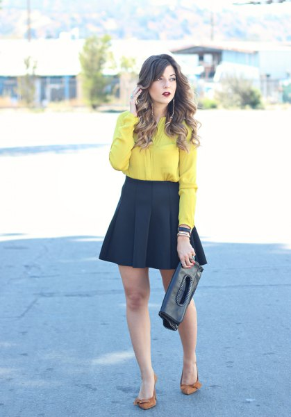 yellow shirt with buttons and black, flared mini and pleated skirt