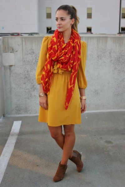 yellow mini dress with fit and flare with orange-gold scarf