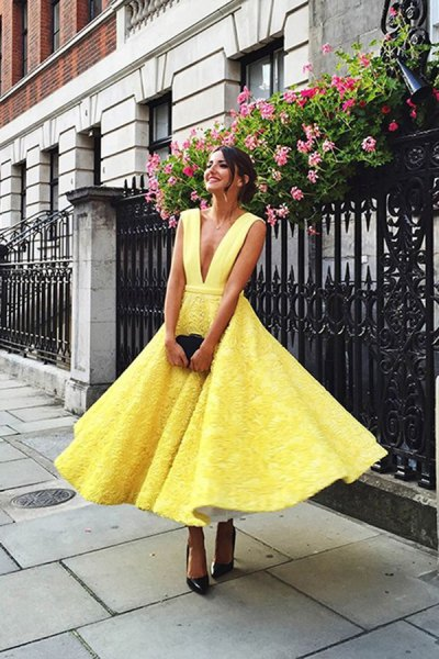 yellow lace fit and flare midi dress with deep V-neckline and black heels