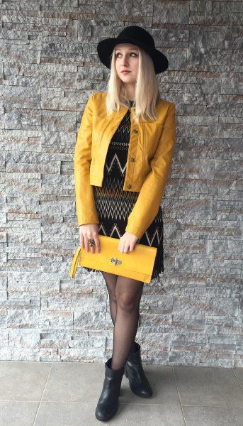 yellow leather jacket, black sheath dress printed with tribal