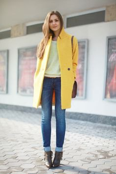 yellow long wool coat with white sweater and cuffed jeans