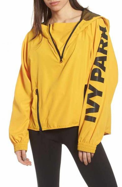 yellow windbreaker with sweater and black running shorts
