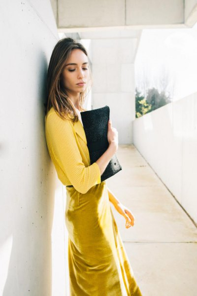 yellow ribbed sweater with mustard midi dress and black leather clutch